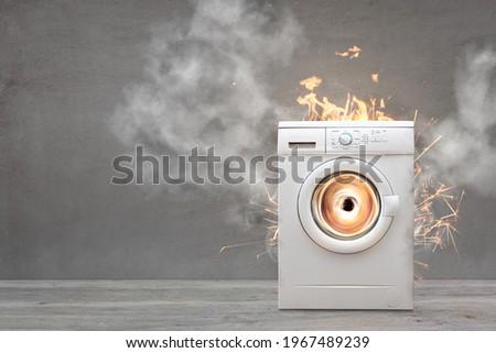 Broken Washing Machine With Smoke And Fire Royalty-Free Stock Photo #1967489239