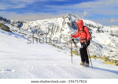 Woman hiker ascends a snow covered trail in winter #196757816