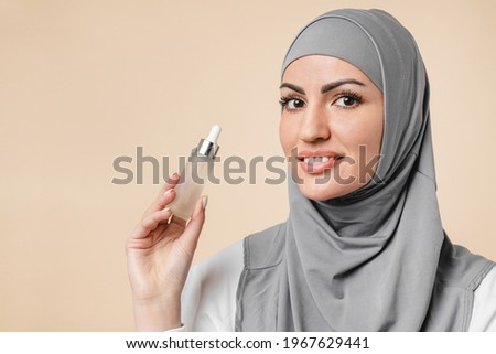 Young pretty arabian muslim islamic woman in hijab using beauty serum for anti-age effect, rejuvenation and pampering. Soft skin, makeup base and cosmetics concept Royalty-Free Stock Photo #1967629441