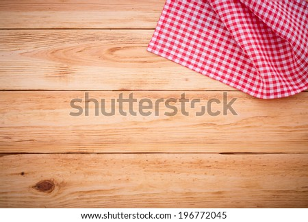 Wood texture background. Wooden table covered with tablecloth cloth checkered plaid red. View from top. Empty tablecloth for product montage for recording menu, recipe. Free space for your text  #196772045