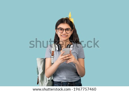 Positive Indian teen student with backpack, smartphone and headphones participating in online lesson on blue studio background. Happy adolescent teenage girl with mobile device having remote education Royalty-Free Stock Photo #1967757460