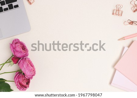 Feminine workspace for online work with laptop, rose flowers, office supply on a beige background. Distance study concept with place for text. Royalty-Free Stock Photo #1967798047