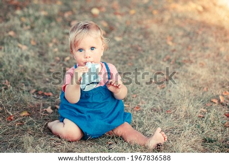 Toddler baby eating baby food organic vegetable fruit puree from pouch. Supplementary solid healthy food meal snack for babies kids. Girl eating outdoor in park on summer day.  Royalty-Free Stock Photo #1967836588