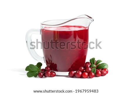Homemade fresh wild lingonberry sauce in glass gravy boat isolated on white background