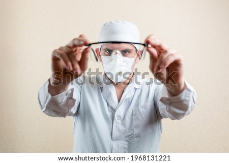 Doctor in goggles and a mask, on a light background. High quality photo Royalty-Free Stock Photo #1968131221