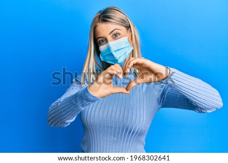 Beautiful blonde woman wearing covid-19 medical mask smiling in love showing heart symbol and shape with hands. romantic concept.