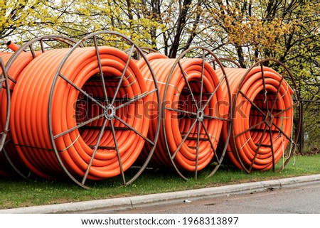 Spools of orange fiber optic conduit on a mobile reel for fiber optic cable installation Royalty-Free Stock Photo #1968313897