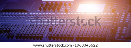 Audio mixing console with faders and adjusting knobs, Sound mixer with motorized faders, Professional audio studio sound mixer console board panel with recording, TV equipment. Blue tone and close-up