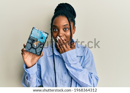 African american woman with braided hair holding hard disk covering mouth with hand, shocked and afraid for mistake. surprised expression