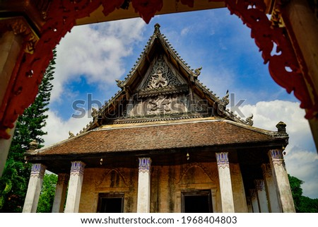 Public Thai temple landscape picture in sunlight, background with blue sky. The heritage historical of religion travel landmark. The roof of temple made from wood with beautiful art pattern.