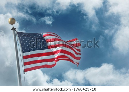 Flag of the United States of America over blue sky white clouds background Royalty-Free Stock Photo #1968423718
