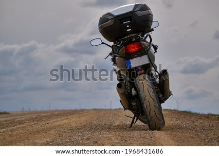 Enduro motorcycle traveler alone under a blue sky with white clouds. Royalty-Free Stock Photo #1968431686