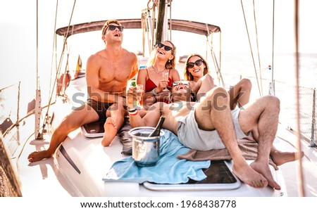 Happy young friends having fun at sailboat party - Wanderlust travel concept with millenial people on sailing trip - Luxury lifestyle on exclusive summer mood - Warm sunshine halo filter Royalty-Free Stock Photo #1968438778