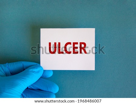 Medical and stomach ulcer symbol. Doctor hand. White card with the word 'ulcer'. Beautiful blue background. Doctor hand in blue glove. Medical and stomach ulcer concept. Copy space.