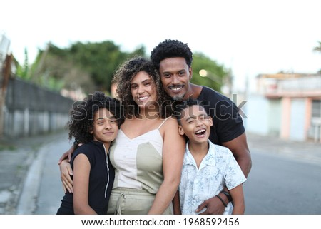 Brazilian family posing for photo looking at camera. Father, wife and children together Royalty-Free Stock Photo #1968592456