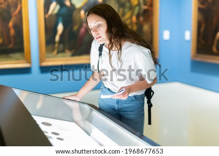 Attentive girl visitor at the museum looks at the exposition behind a glass display case, holding an information ..booklet Royalty-Free Stock Photo #1968677653