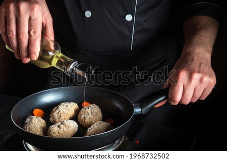 Cooking beef cutlets in grill pan with the hands of cook on black background for copying the space text restaurant menu. Chef  dds oil
