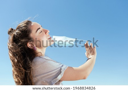 Breathing and feeling free during Coronavirus pandemic concept. Young woman removing a protective surgical mask. Royalty-Free Stock Photo #1968834826