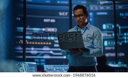 Young Multiethnic Male Government Employee Uses Laptop Computer in System Control Monitoring Center. In the Background His Coworkers at Their Workspaces with Many Displays Showing Technical Data. Royalty-Free Stock Photo #1968876016
