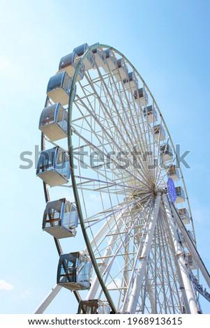 Ferris wheel against the blue sky. Modern Ferris wheel. Royalty-Free Stock Photo #1968913615