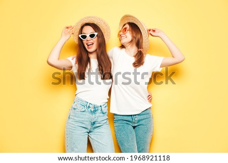 Two young beautiful smiling hipster female in trendy summer white t-shirt and jeans clothes.Sexy carefree women posing near yellow wall in studio.Positive models in hats.Dancing at party