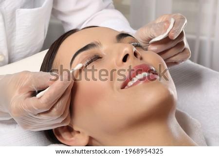 Young woman undergoing eyelash lamination in salon, closeup Royalty-Free Stock Photo #1968954325