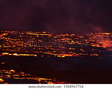 Stunning view of glowing lava flows at volcano eruption site in Geldingadalir valley near Fagradalsfjall mountain, Grindavík, Reykjanes, Iceland in the dark. Picture blurred due to hot shimmering air.