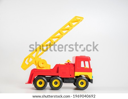 Children's toy plastic car isolated on white background. Red fire truck.