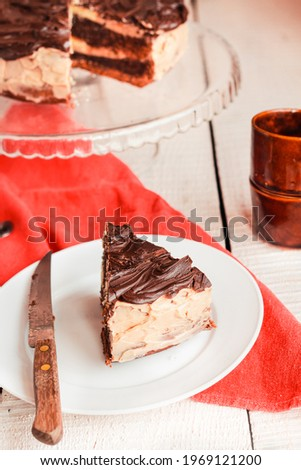 Dark chocolate cake with Coffee slice with chocolate buttercream frosting on a white plate.Selective focus. Royalty-Free Stock Photo #1969121200