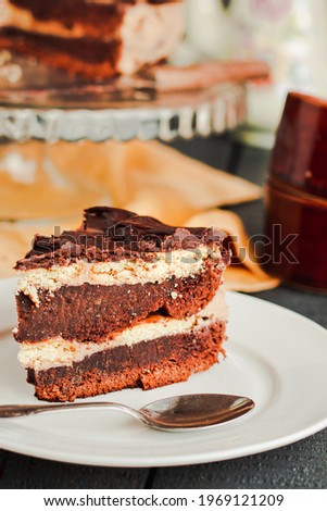 Dark chocolate cake with Coffee slice with chocolate buttercream frosting on a white plate.Selective focus. Royalty-Free Stock Photo #1969121209