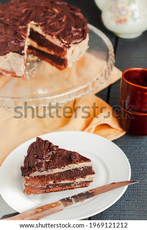 Slice of three chocolate cake ona white plate. Board with delicious tasty homemade cake on table. Blue gray wooden background. Selective focus. Royalty-Free Stock Photo #1969121212