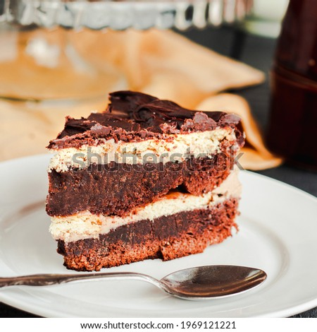 Slice of chocolate layered birthday cake close-up on blue gray wooden background. Homemade Chocolate frosting dessert.Insta-size. Royalty-Free Stock Photo #1969121221