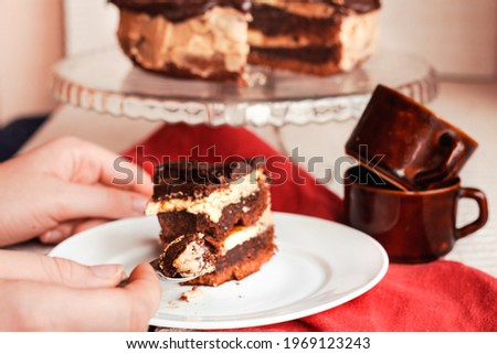 Slice of three chocolate cake on a plate. Delicious tasty homemade cake on table. White wooden background. Young woman eating dessert process. Royalty-Free Stock Photo #1969123243