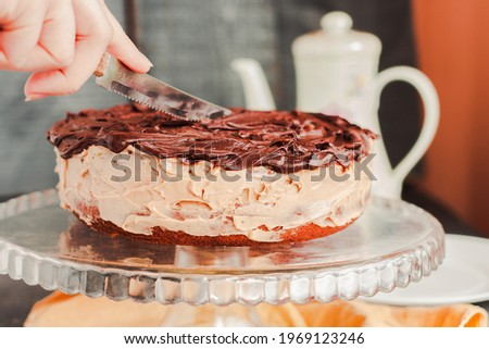 Delicious round cake with white buttercream topped with chocolate frosting, icing. Woman hands cuting it. Royalty-Free Stock Photo #1969123246