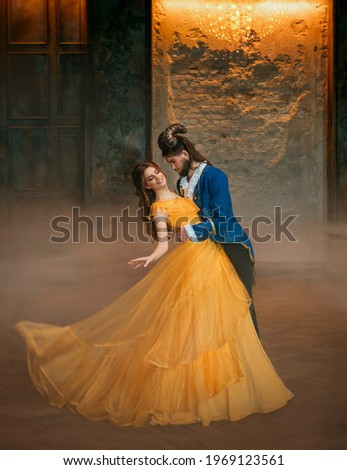 loving couple is dancing at fairy ball. Happy beauty woman fantasy princess in yellow dress and guy is enchanted guy, horns on head Girl whirls in arms of male prince. Man monster carnival costume Royalty-Free Stock Photo #1969123561