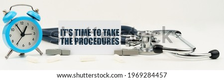 Medicine and health concept. On an isolated white background there is a clock, a stethoscope and a business card with the inscription - It s time to take the procedures