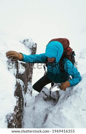 Mountaineer using an ice axe to climb Forcan Ridge in Glen Shiel, Scotland Royalty-Free Stock Photo #1969416355