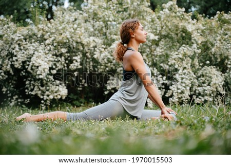 Young woman with red hair trains, doing exercises in yoga pose of a rider outdoors in the park. Royalty-Free Stock Photo #1970015503