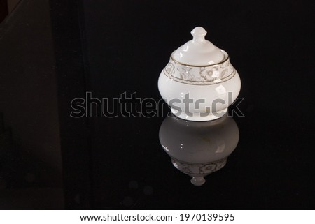 closeup picture of old ceramic sugar pot on reflective tabletop