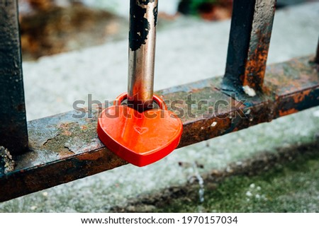 A red heart-shaped lock symbolizing love is locked on a rusty iron railing with moss
