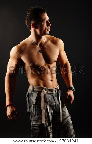 Handsome muscular man poses on the dark background #197031941
