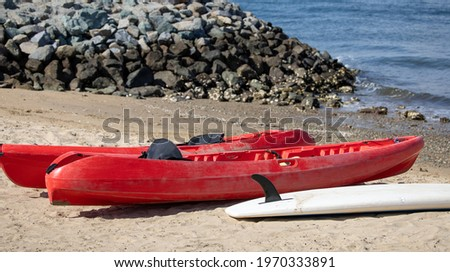 Two red kayaks and a paddle board by the shore. Water activities equipment.