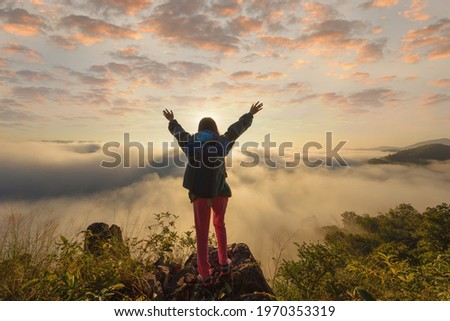 female hiker on top hills with arms out durin sunrise,cheering woman hiker open arms at mountain peak Royalty-Free Stock Photo #1970353319