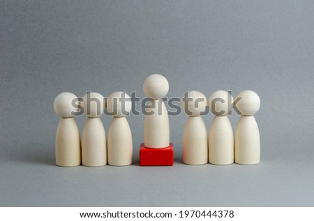Team and leader on a pedestal on a gray background. Wooden figures in the image of people. Chief at work, leadership and personnel management, business concept. Royalty-Free Stock Photo #1970444378