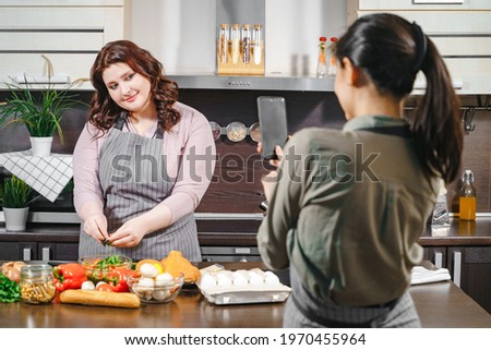 Two girlfriends recording a video or taking a photo on a smartphone for social networks. Plus size female blogger making blog content about diet and healthy food in the kitchen.