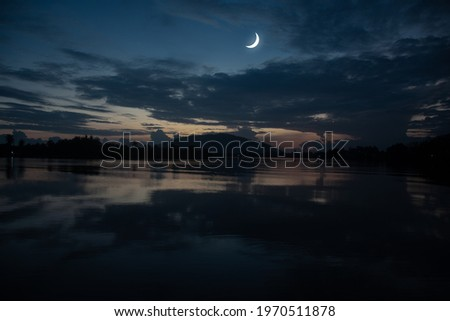 Concept the crescent moon the symbol of Islam begins the eid al Fitr. Seeing the moon in the night sky. The evening sky and the vast river in darkness are beautiful. Royalty-Free Stock Photo #1970511878