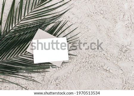 Blank horizontal card mock-up and craft envelope on green date palm leaves. Summer stationery still life scene. Sandy beach background or desert. Flat lay, top view. Tropical vacation concept, nobody. Royalty-Free Stock Photo #1970513534