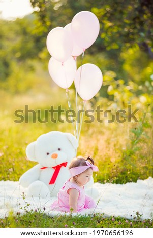 girl sitting in nature with teddy bear and balloons
