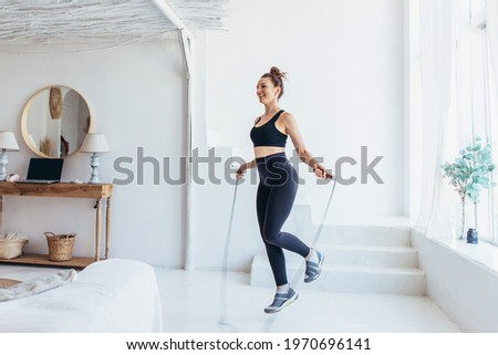 Fit woman with jump rope at home doing skipping workout. Royalty-Free Stock Photo #1970696141
