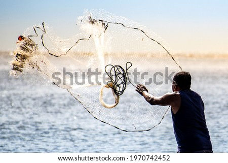 A fisherman casting a net into the water during on a golden horizon Royalty-Free Stock Photo #1970742452
